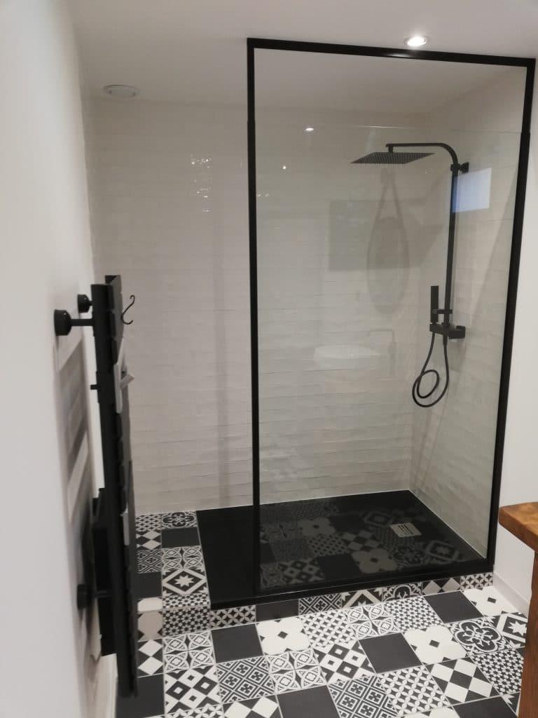 espace douche avec bac à douche en résine et sa paroi fixe. Mitigeur thermostatique et sa pluie. Sèche serviette soufflant